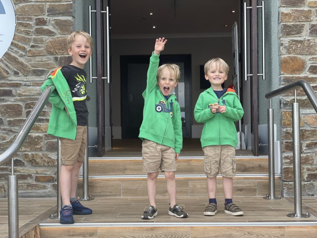 Three brothers wearing shorts and green hoodies cheer on the steps of the Esplanade hotel in newquay