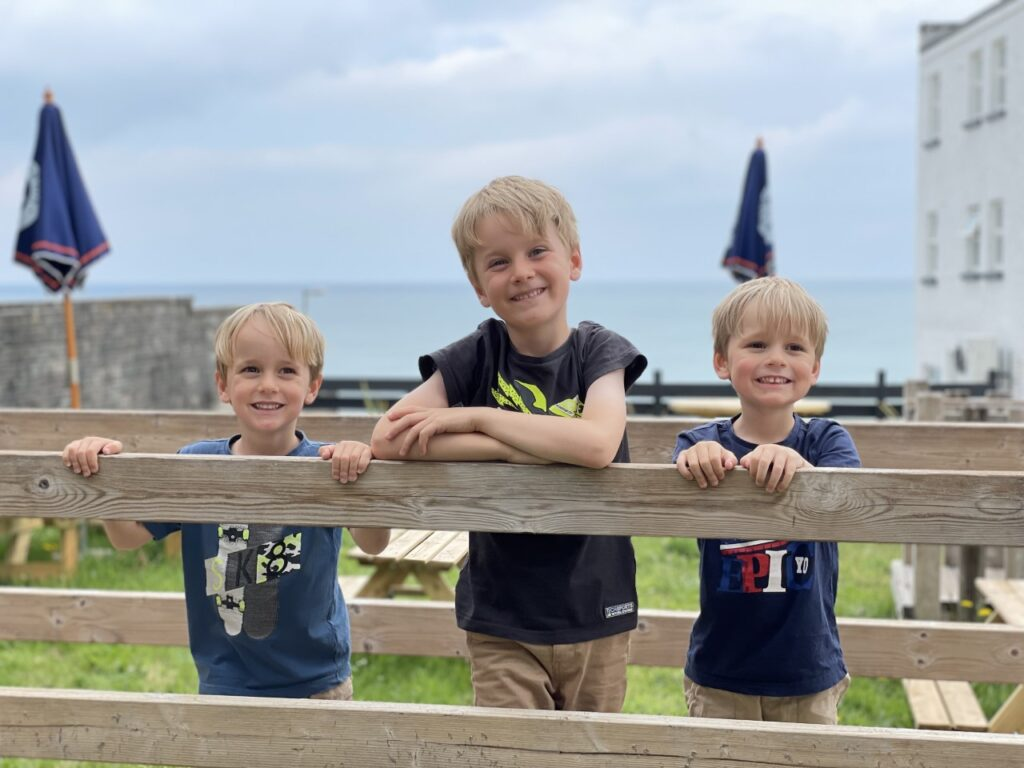 Three young brothers stand on a wooden wobbly bridge in a pirate play park at a family friendly hotel in cornwall