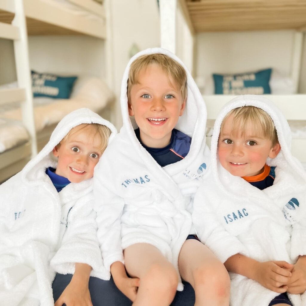 Three young brothers wear white fluffy robes with hoods up