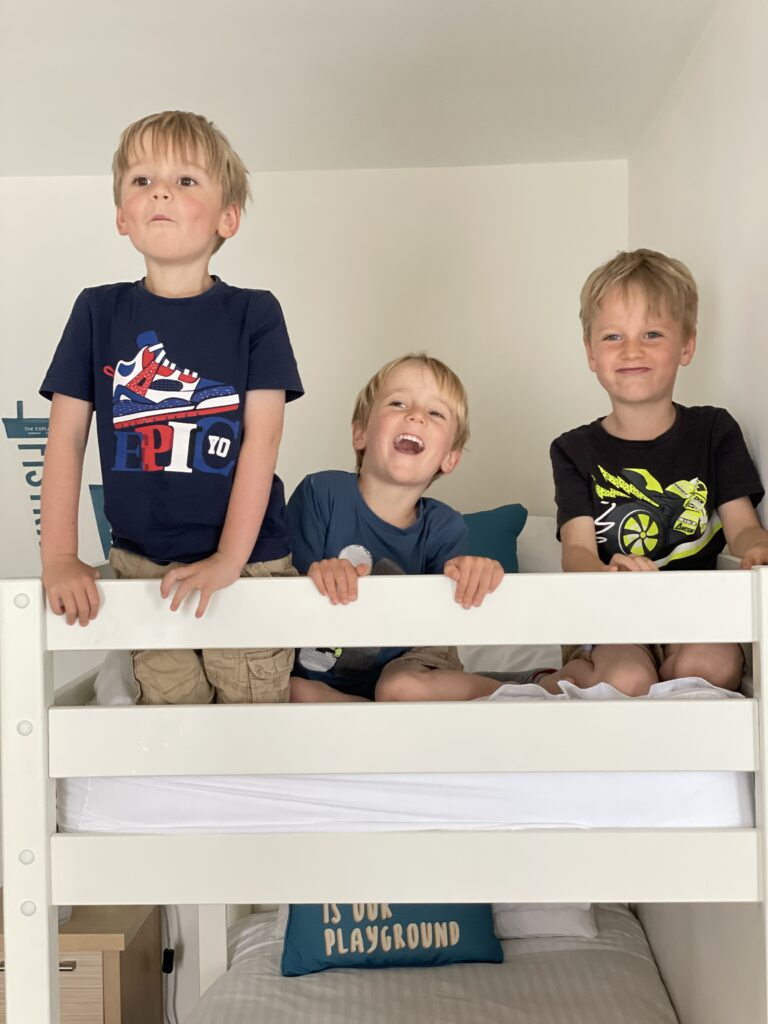 Four year old twins and six year old boy all sit on the top of a bunk bed