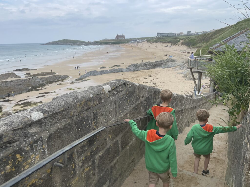 Three young boys in shorts and green hoodies walk down a flight of steps to Fistral beach in cornwall