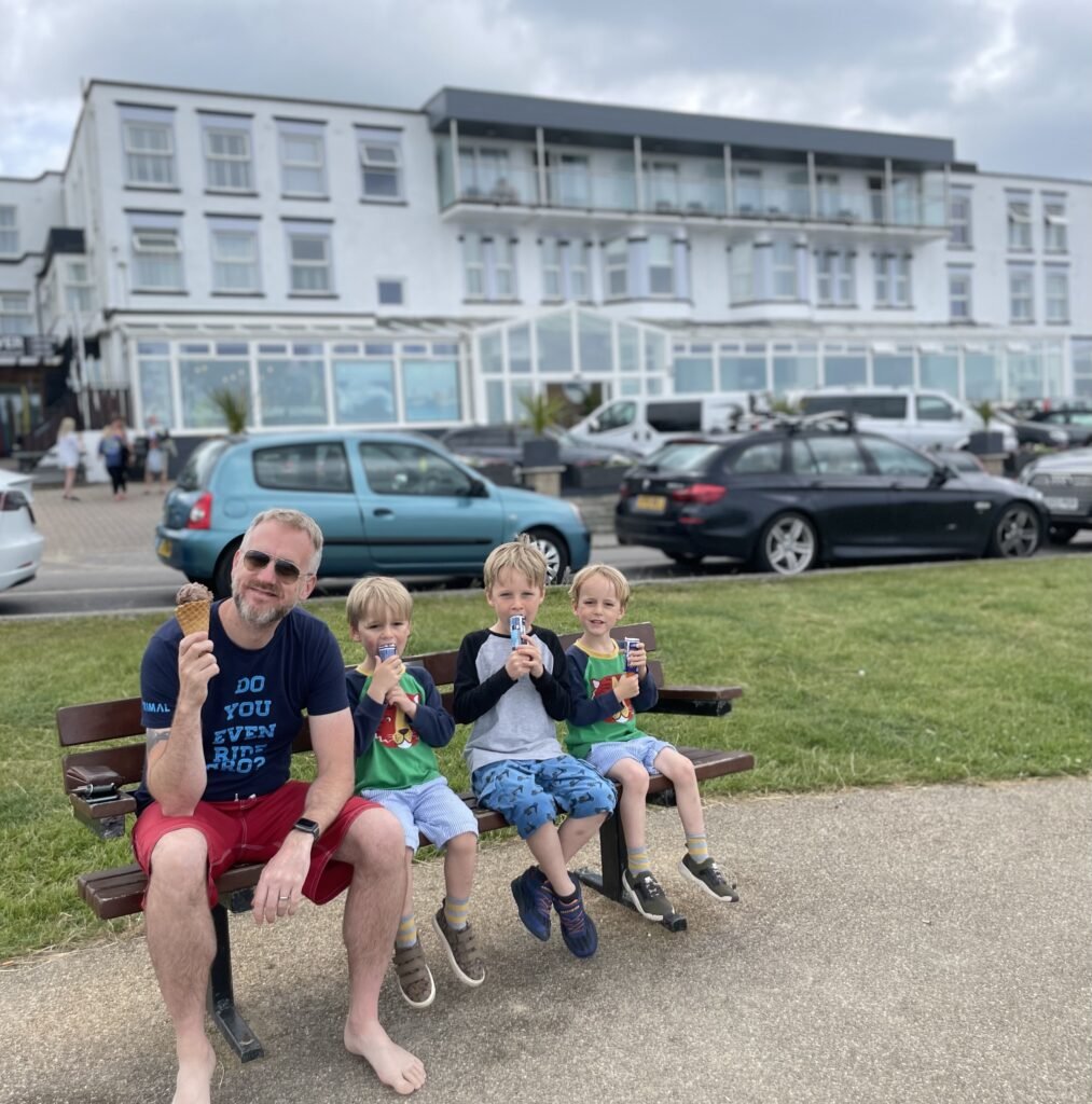 Three boys and their dad sit on a bench outside the Esplanade hotel in Newquay eating ice creams