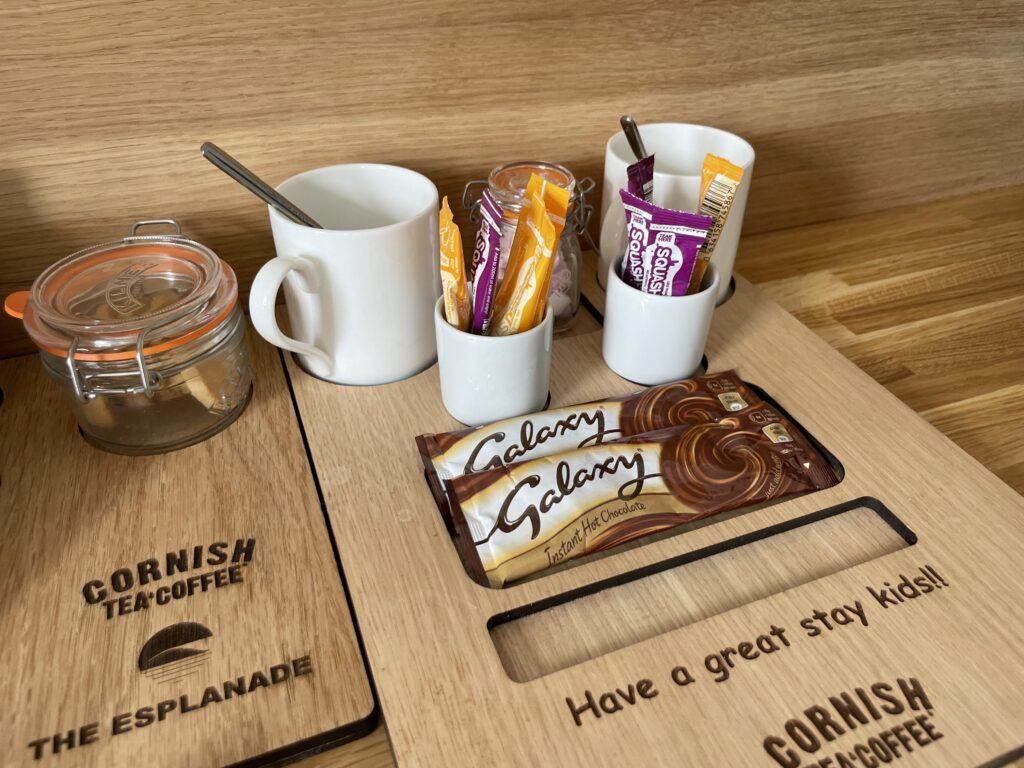 A wooden board containing sachets of squash and hot chocolate, and marshmallows at the Esplanade Hotel