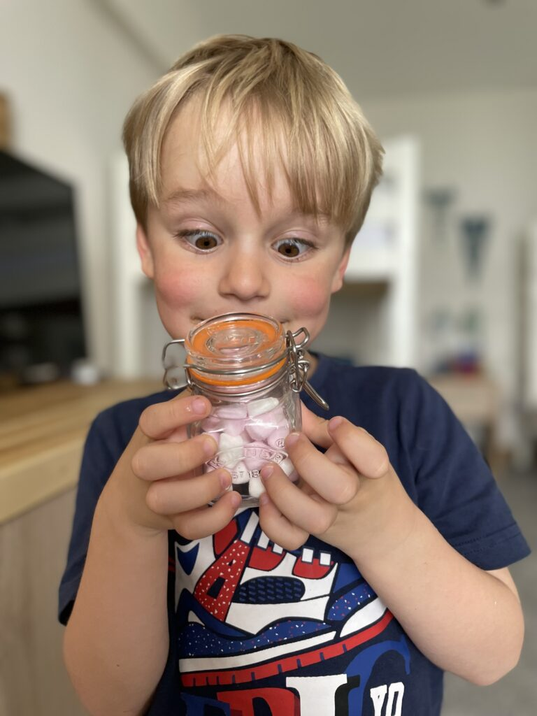 Four year old boy looking excitedly at a jar of mini marshmallows he's holding