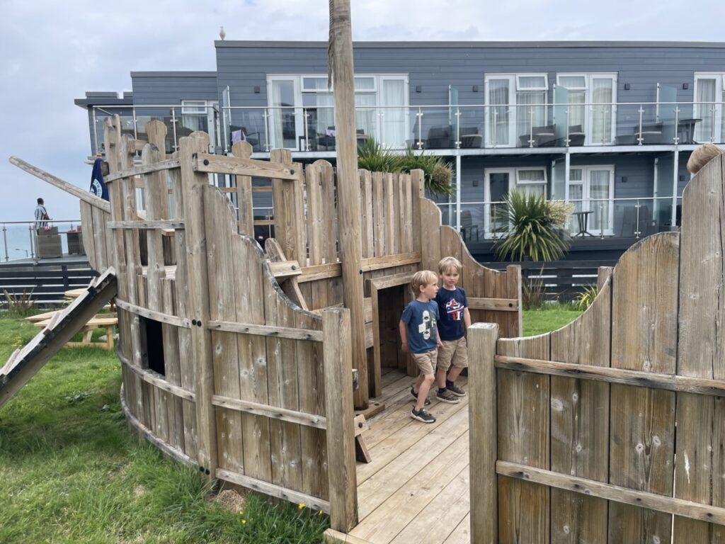 Twin four year old boys play in a pirate ship