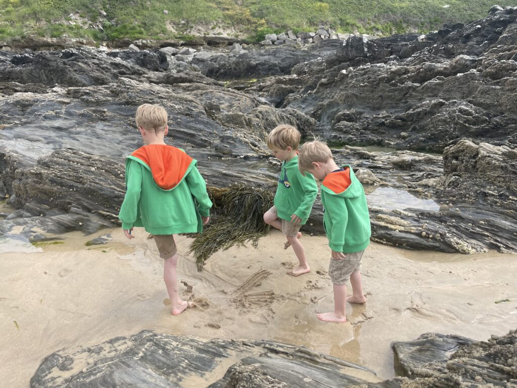 Three young boys in shorts and green hoodies play in rockpools on Fistral Beach in Cornwall