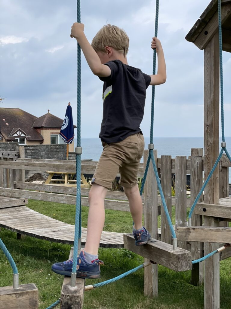 Six year old boy plays on a wooden play area