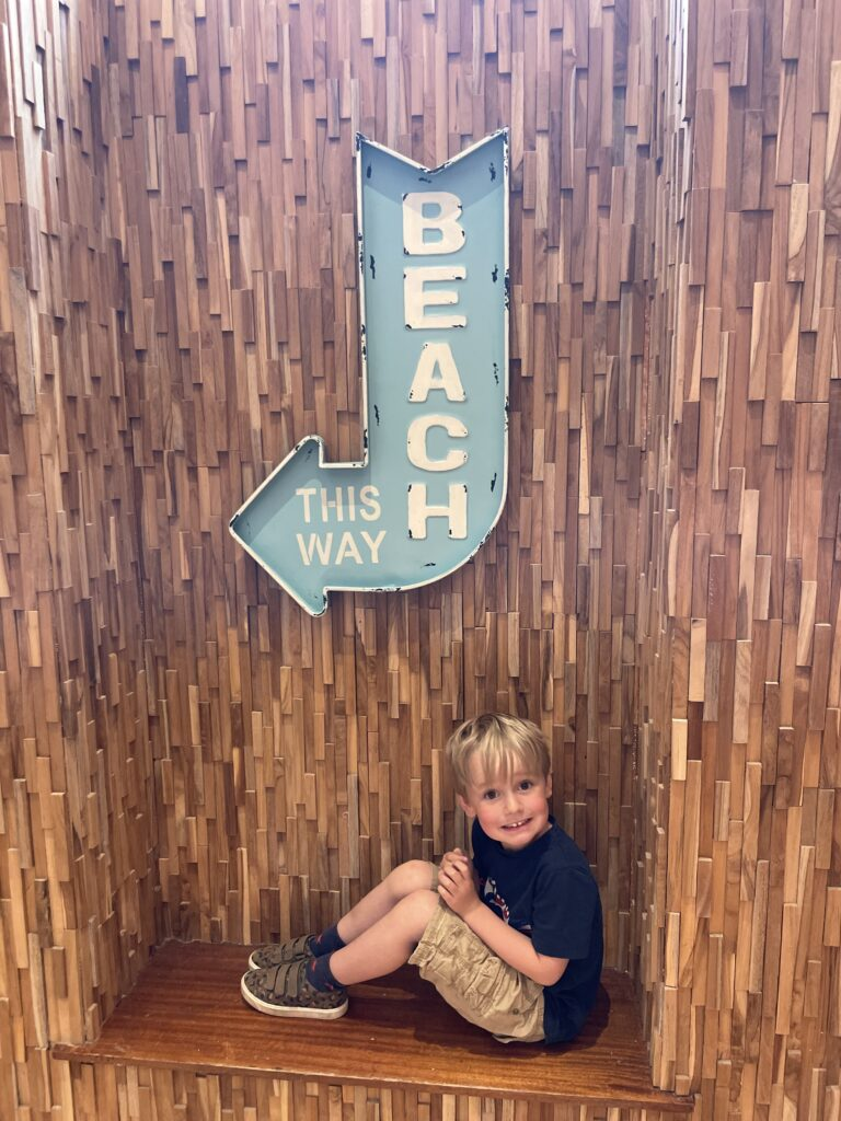 Four year old boy sits on a bench under a 'this way to the beach' sign at the Esplanade hotel in Newquay