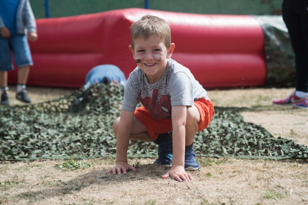 A boy wearing war pain on his face plays on an inflatable