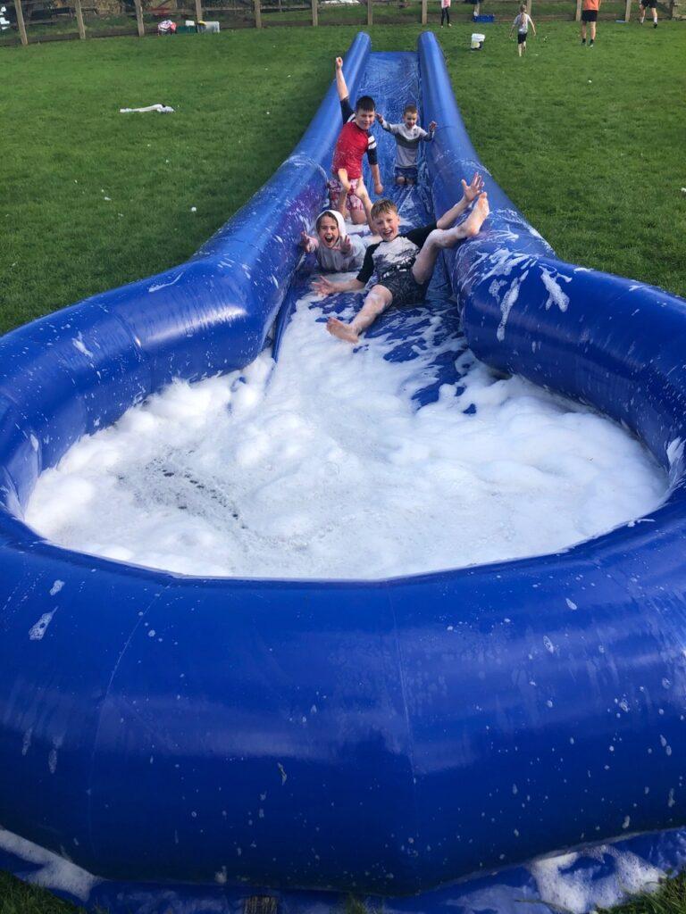 Children go down a slip n slide at a High 5 summer camp in Plymouth