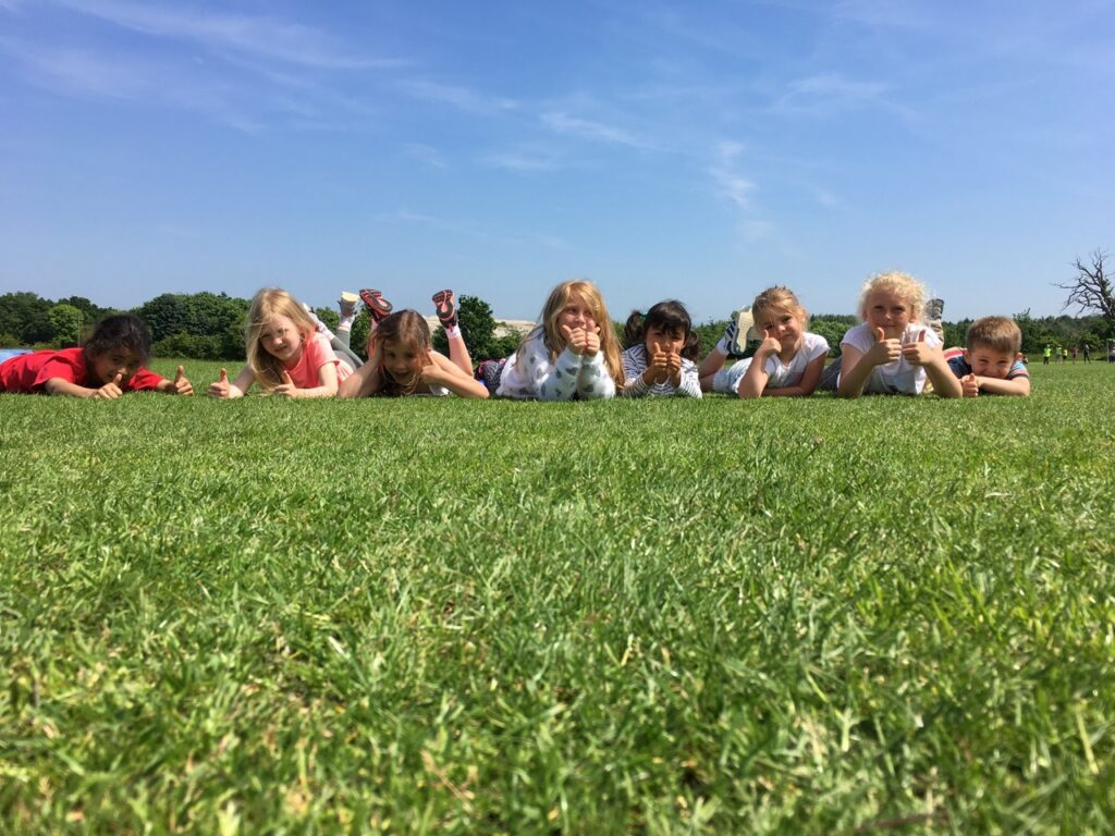 Children lay on the grass at a High 5 summer camp in Plymouth