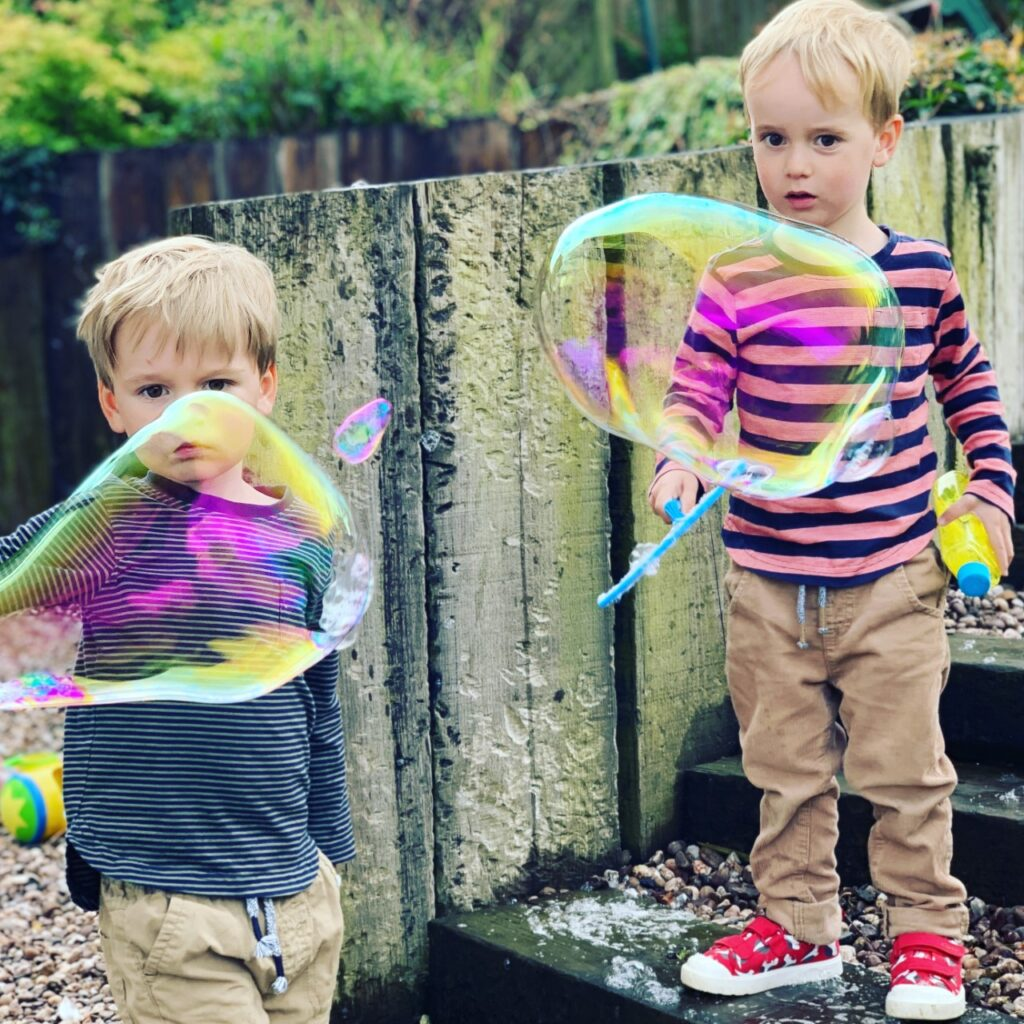 Twin two year olds play with giant bubbles in the garden