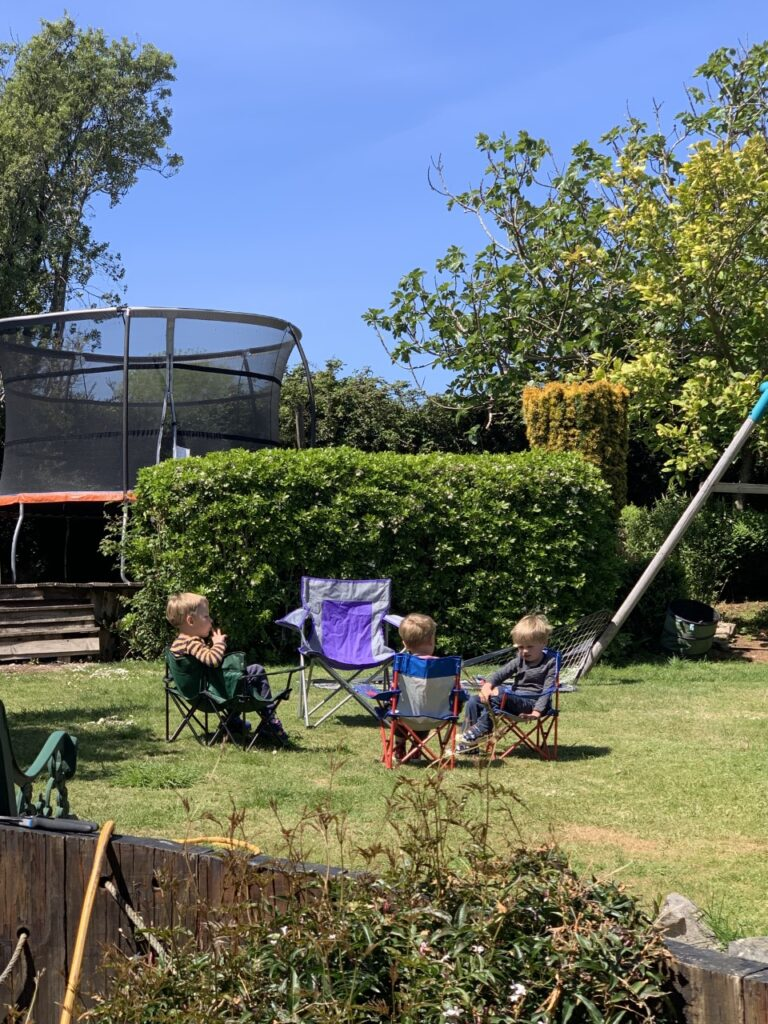Three young brothers having fun in the garden sitting on camping chairs and eating a picnic