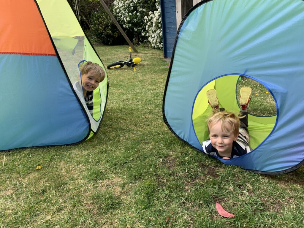 Twin two year olds making the garden fun in pop up tents