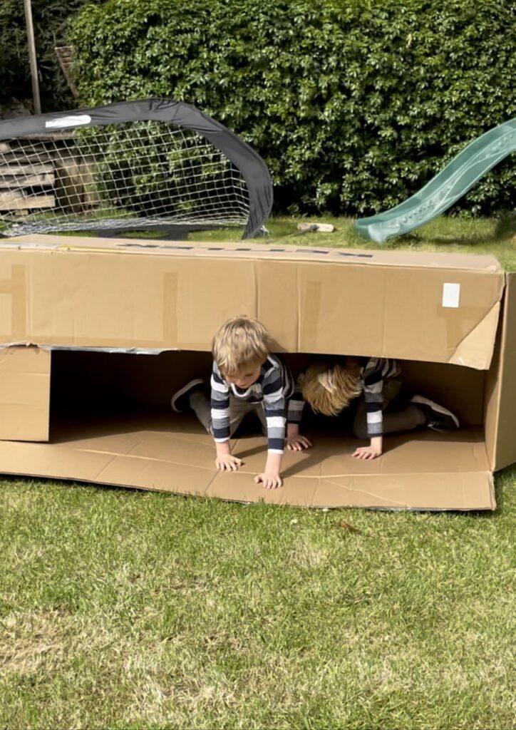 Twin three year old boys play in a giant cardboard box having fun in the garden