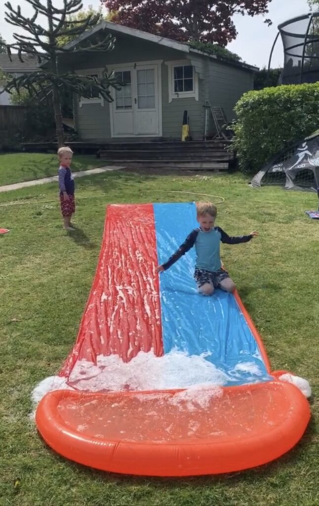 Little boys play on a slip n slide in the garden on a hot day