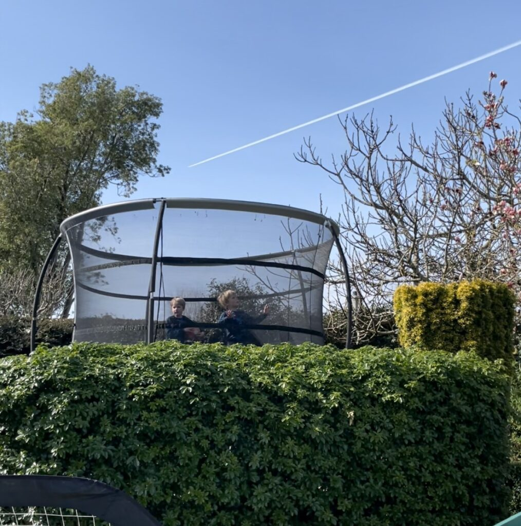Twin three year olds bounce on a large trampoline with a bright blue sky in the background and an aeroplane trail