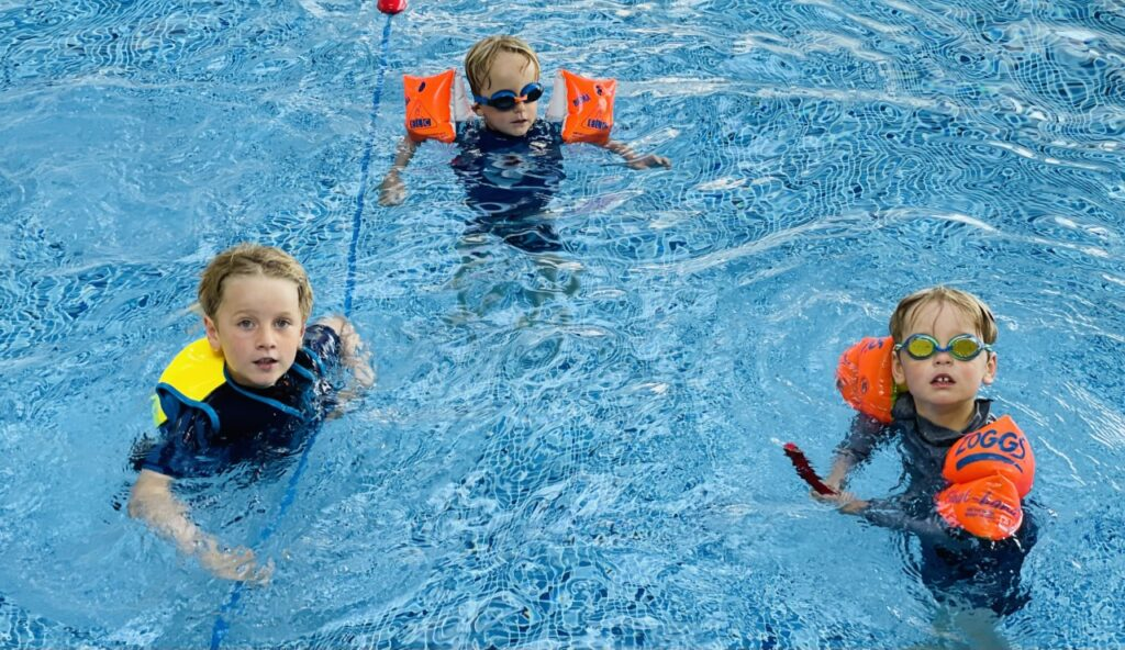 Three brothers in a swimming pool for a piece on summer safety tips