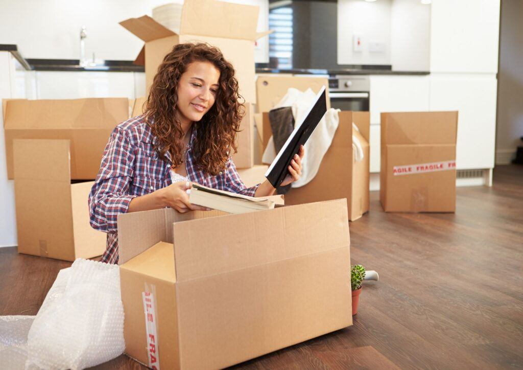 A woman with dark hair sits on the floor unpacking boxes after moving house
