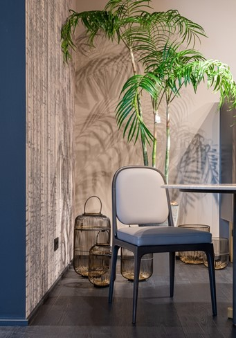 A metal chair and lantern holder cage next to a wooden wall and plant showing off global style decor