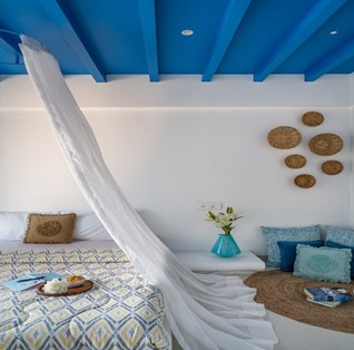 A greek styled bedroom with lots of white linen and blue wooden ceiling