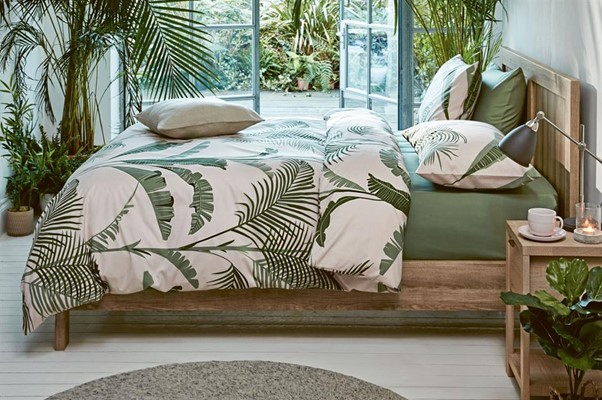 A bed with plants on the duvet cover and green sheets, with plants in the corner of the room in a Tropics style decor