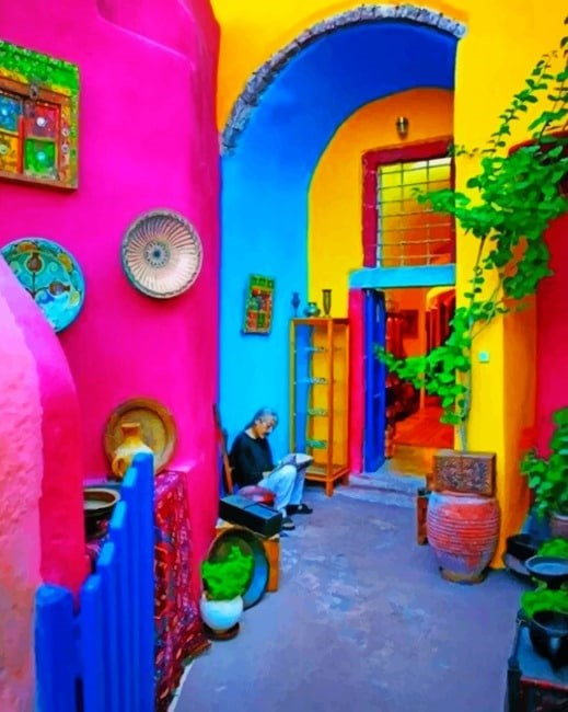A lady sitting on a step surrounded by bright coloured walls in a Mexican style