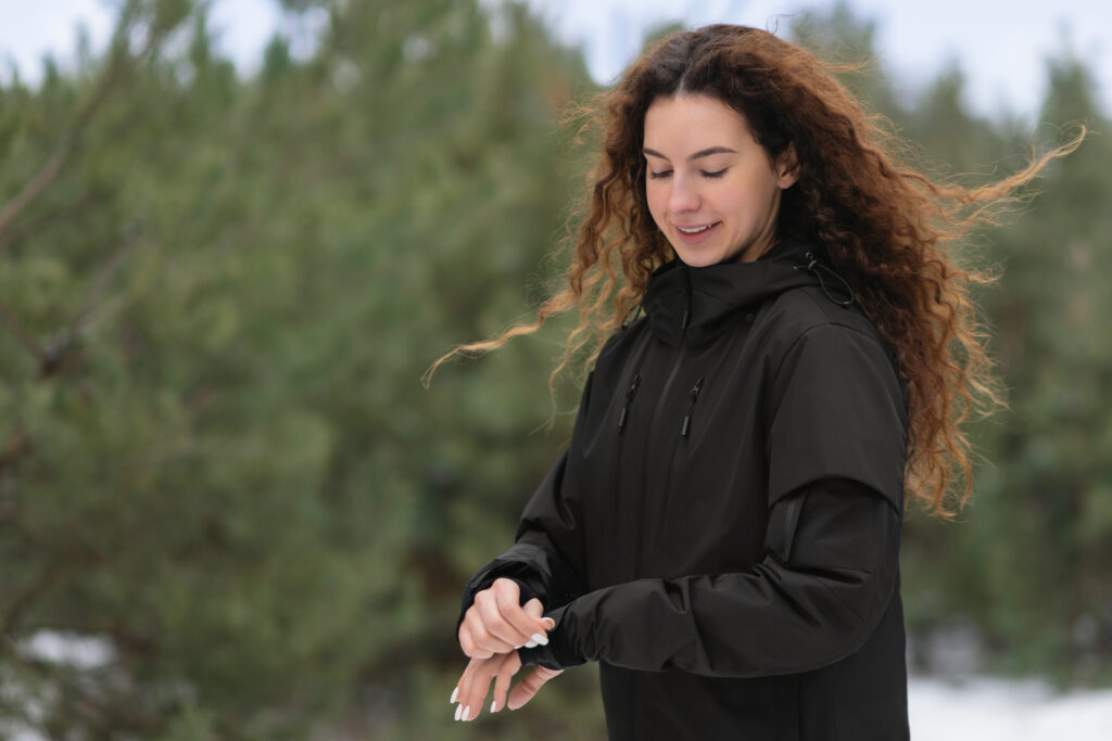 Woman with long dark hair wears a black GAMMA jacket in the woods