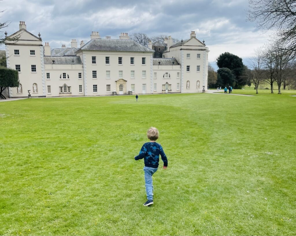 A three year old boy runs across the lawn at Saltram House in Plymouth