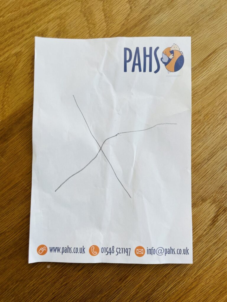 A piece of paper with a cross on it drawn in pencil
