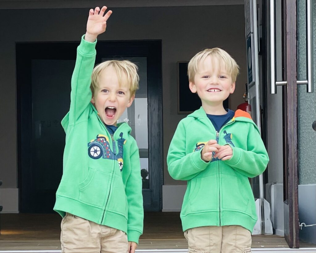 Four year old twin brothers wearing green hoodies smile and cheer in a hotel entrance