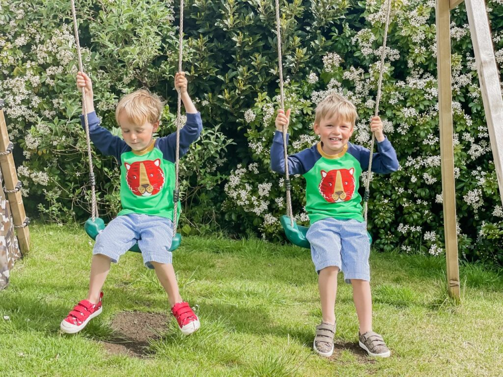 Twin boys wearing shorts and long sleeved tops sit on a double swing set in the garden