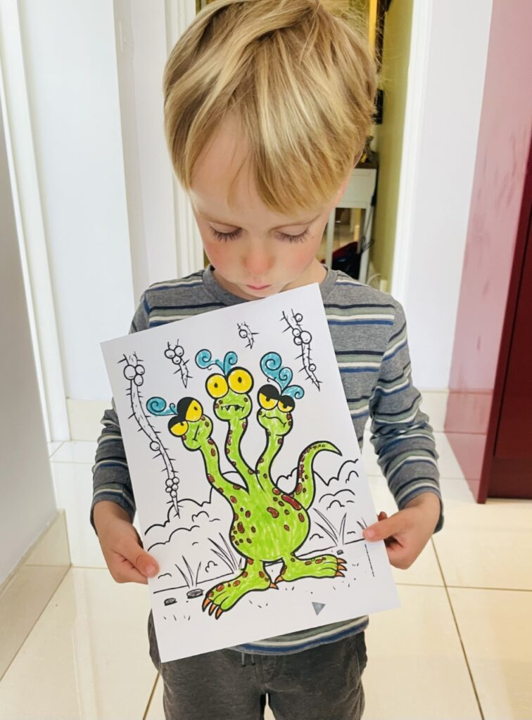 Four year old boy holds up a perfectly coloured in drawing of an octopus monster