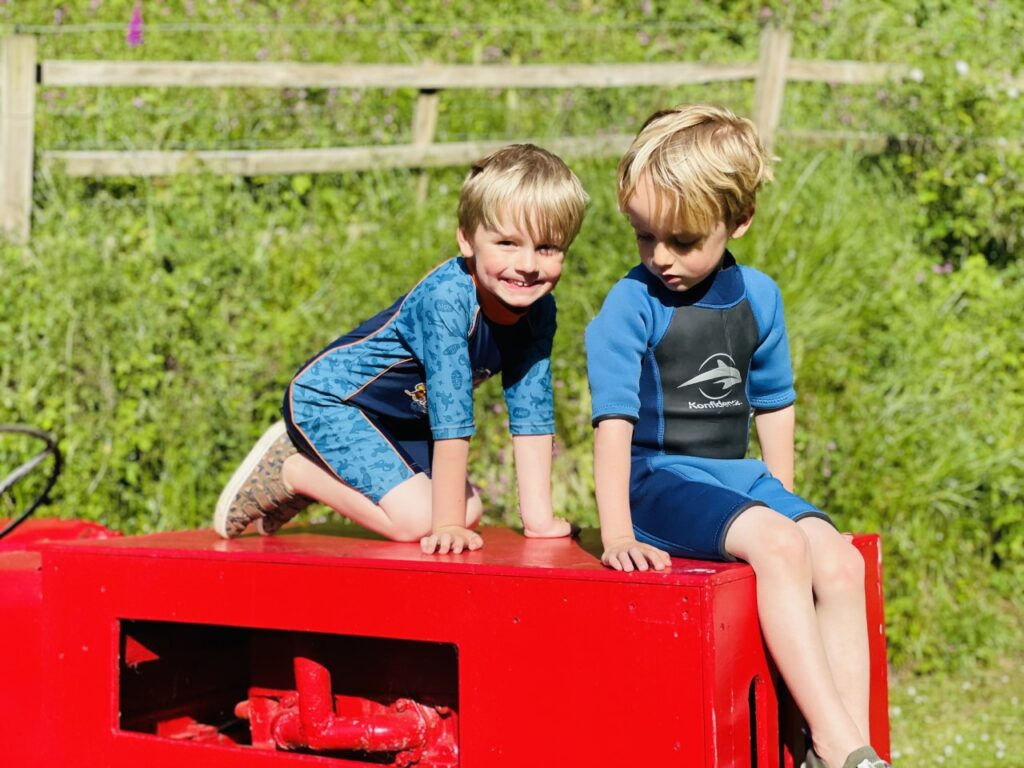 Four year old twin boys in wetsuits sat on the top of a tractor at a park before swimming