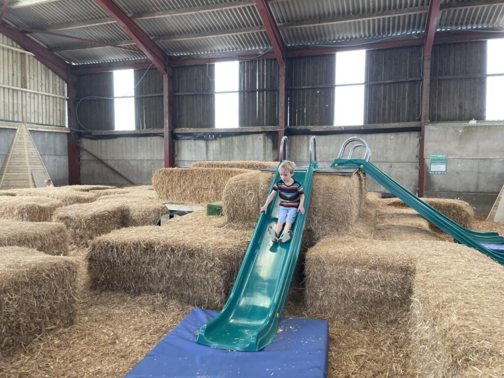 Four year old boy slides down a green slide on top of hay bales at Tapnell Farm Park
