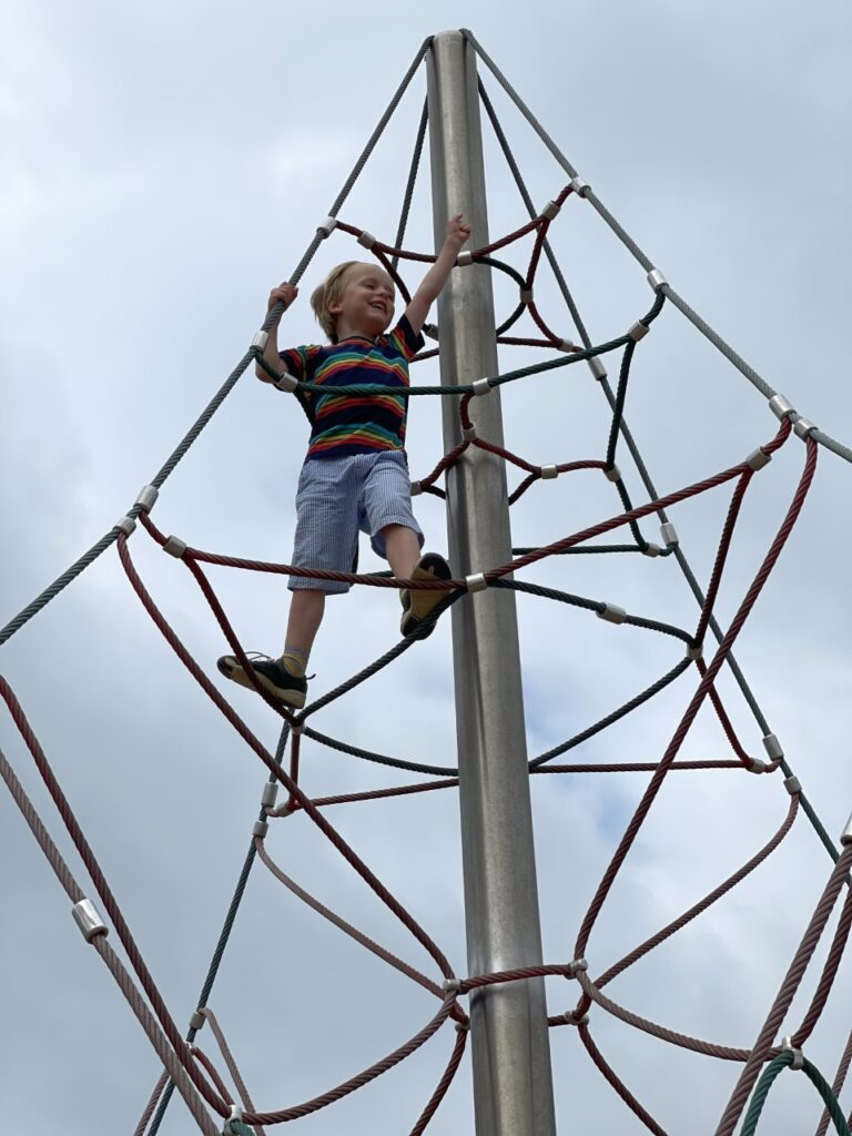 A four year old boy at the top of a Look Out climbing frame