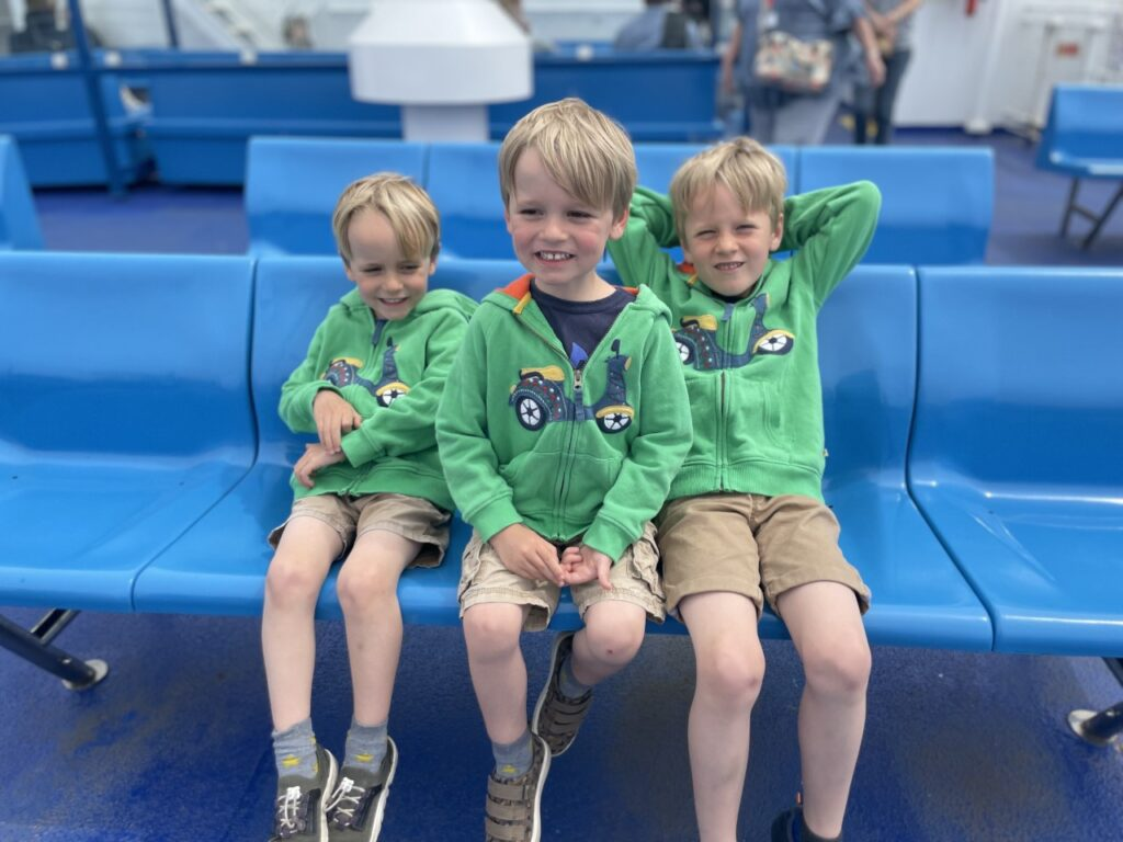 Three brothers wearing green hoodies and shorts sit on a bench on the deck of a Wightlink ferry to the Isle of Wight