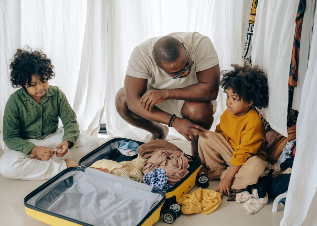 A dad crouched down with two children packing a suitcase talking about shared custody