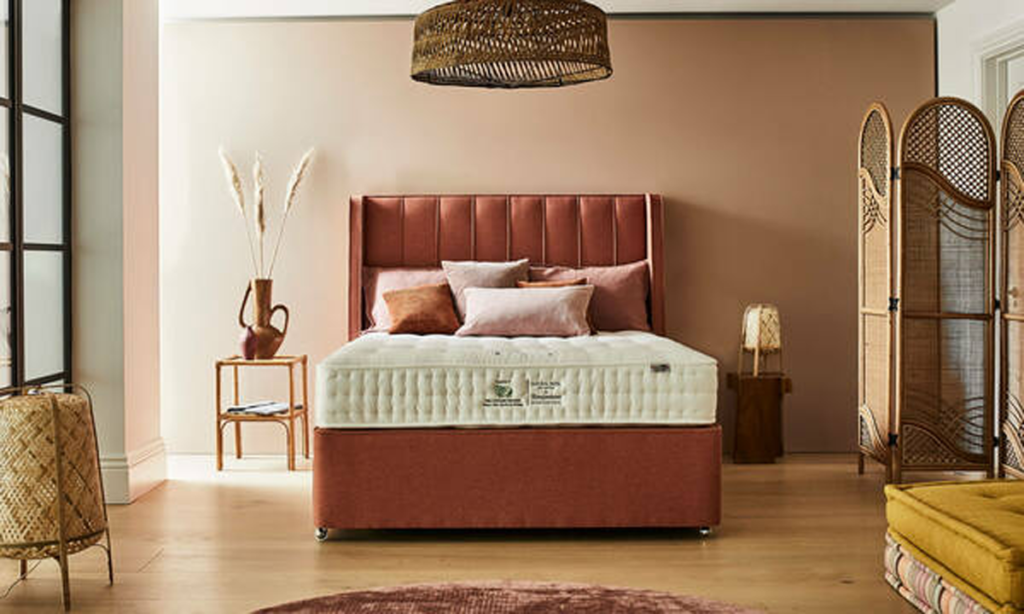 How to update your bedroom in autumn colours, a terracotta coloured bed with autumn coloured walls