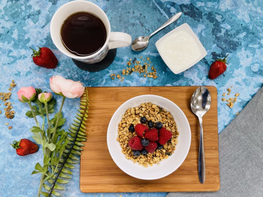 A blue flatlay of a bowl of granola containing good bacteria, a black coffee and some flowers