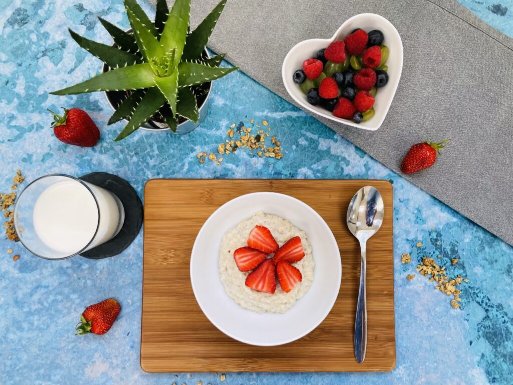 A blue flatlay with a breakfast of porridge containing good bacteria and a bowl of fruit