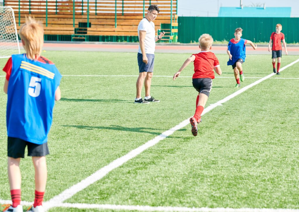 Children doing sports in schools and playing football on a field