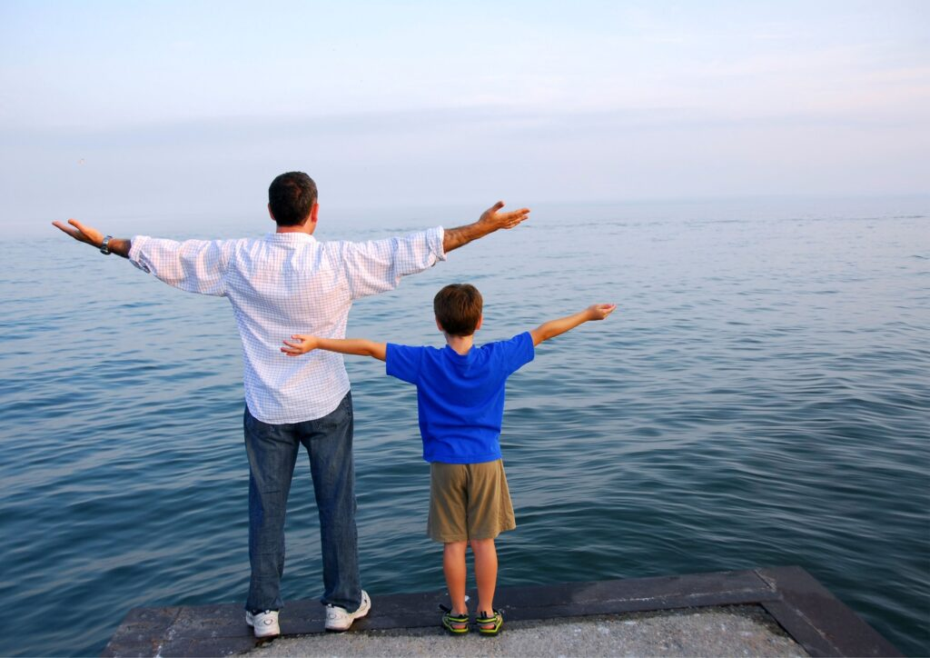 Father and son with arms outstretched overlook the sea for a piece on teaching moral values