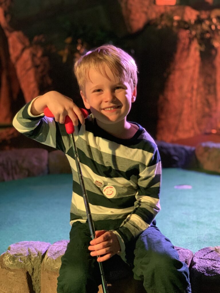 Three year old boy with a golf club at indoor crazy golf in Plymouth