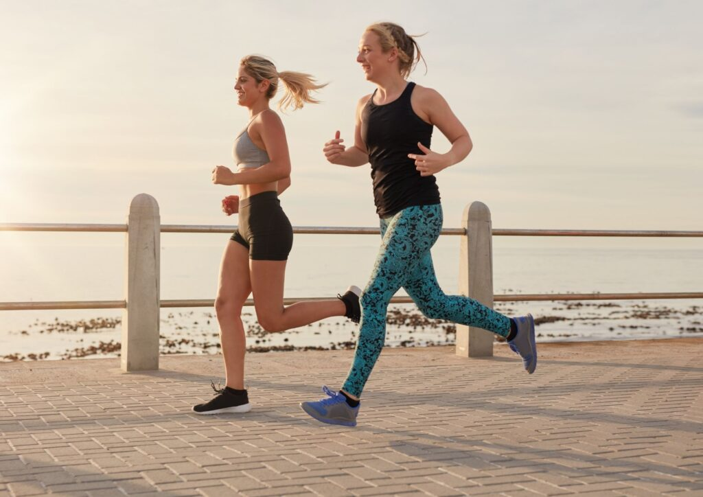 Two women running along a seafront as part of an exercising routine