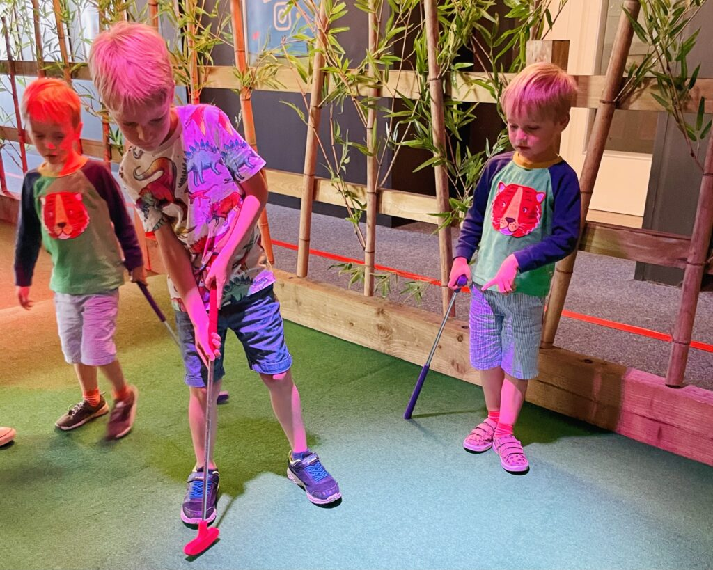 Brothers play golf at Paradise Islalnd Adventure Golf on a family day out at Drake Circus in Plymouth