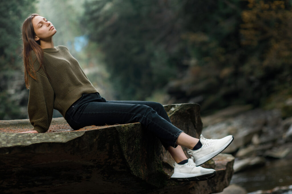Woman with long hair, green jumper, black trousers and white footwear sneakers sits on a rock
