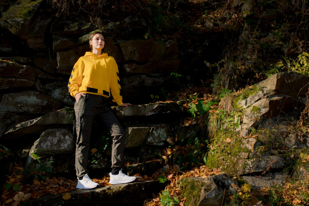 woman in yellow hoodie and black trousers wearing sneakers on rocks in the woods