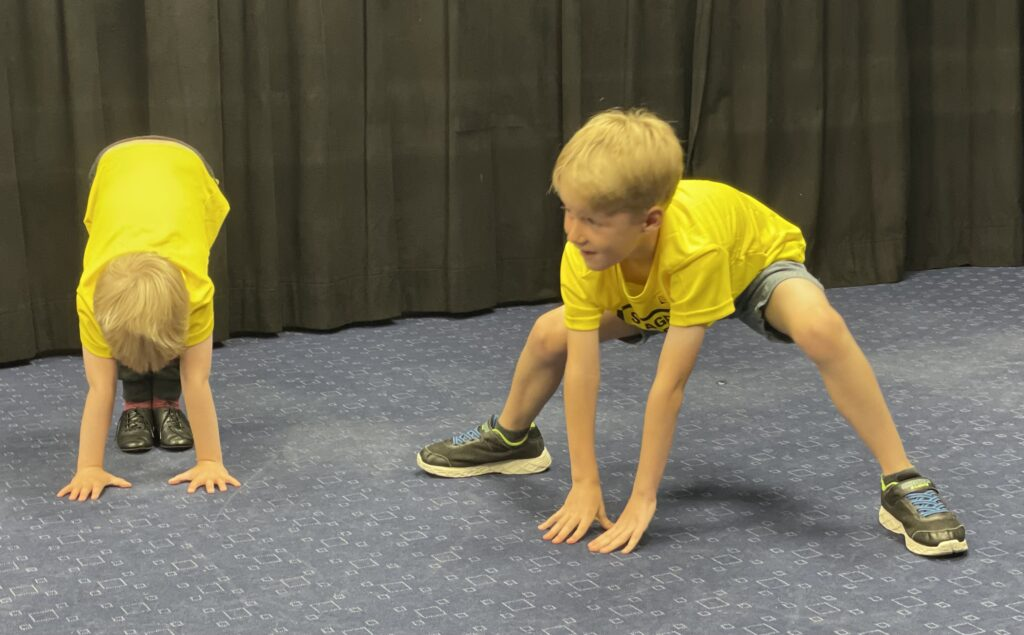 Six year old in a yellow t.shirt with a black background taking part in a Stagecoach performing arts class
