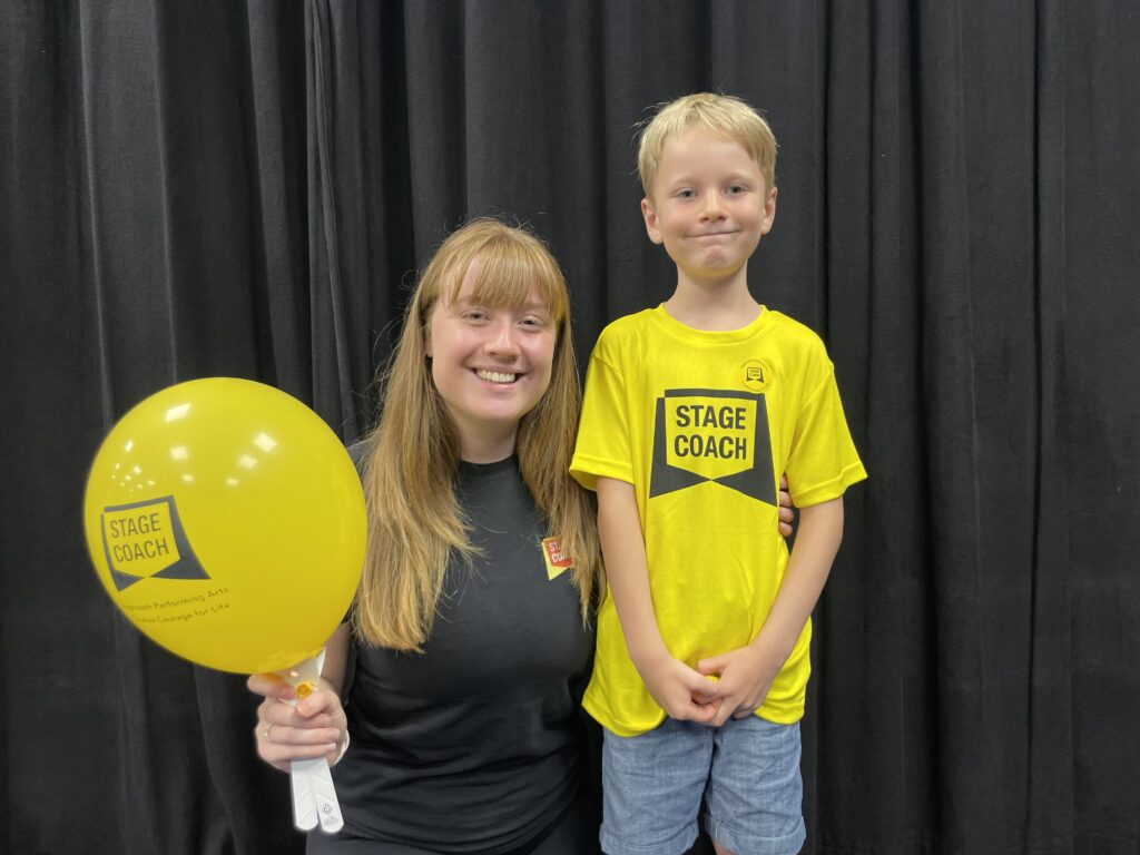 Stagecoach teacher Ellie and six year old pupil with a yellow balloon